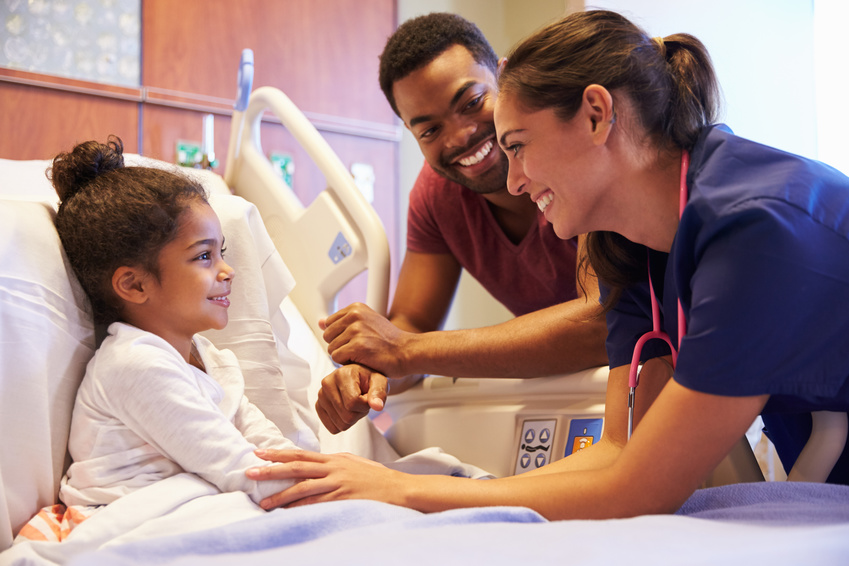 Pediatric Nurse Visiting Father And Child In Hospital Bed