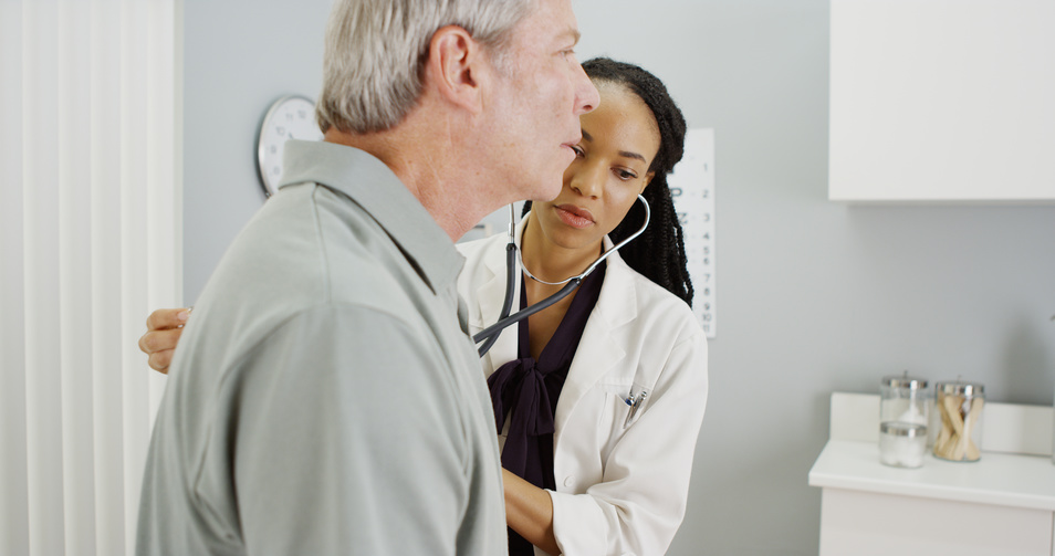 woman doctor listening to senior breathing